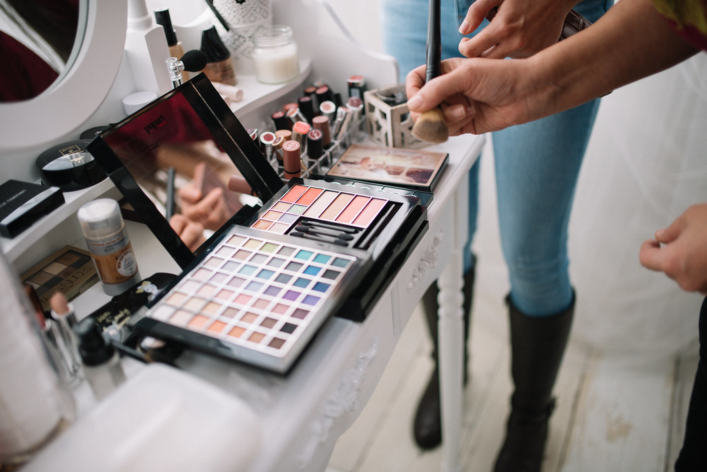 Makeup paletes with multiple different shades on display with a hand holding a brush