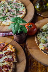 Multiple plates of pizza served on wooden plates on display