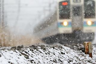 雪降る中の211系