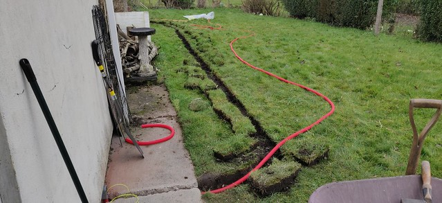 Red polypropylene conduit laid out ready to be placed in the trench