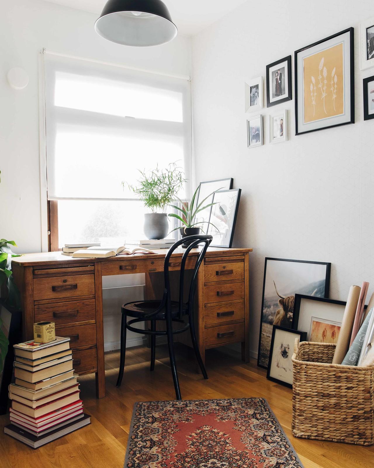 Työhuone, jossa on kirjava matto ja puinen työpöytä. Seinällä on taulukollaasi.