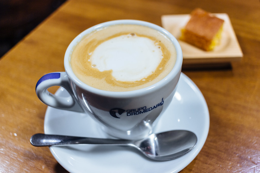A latte in a small ceramic mug sits on a plate with a teaspoon. A small slice of pound cake is on a plate in the background.