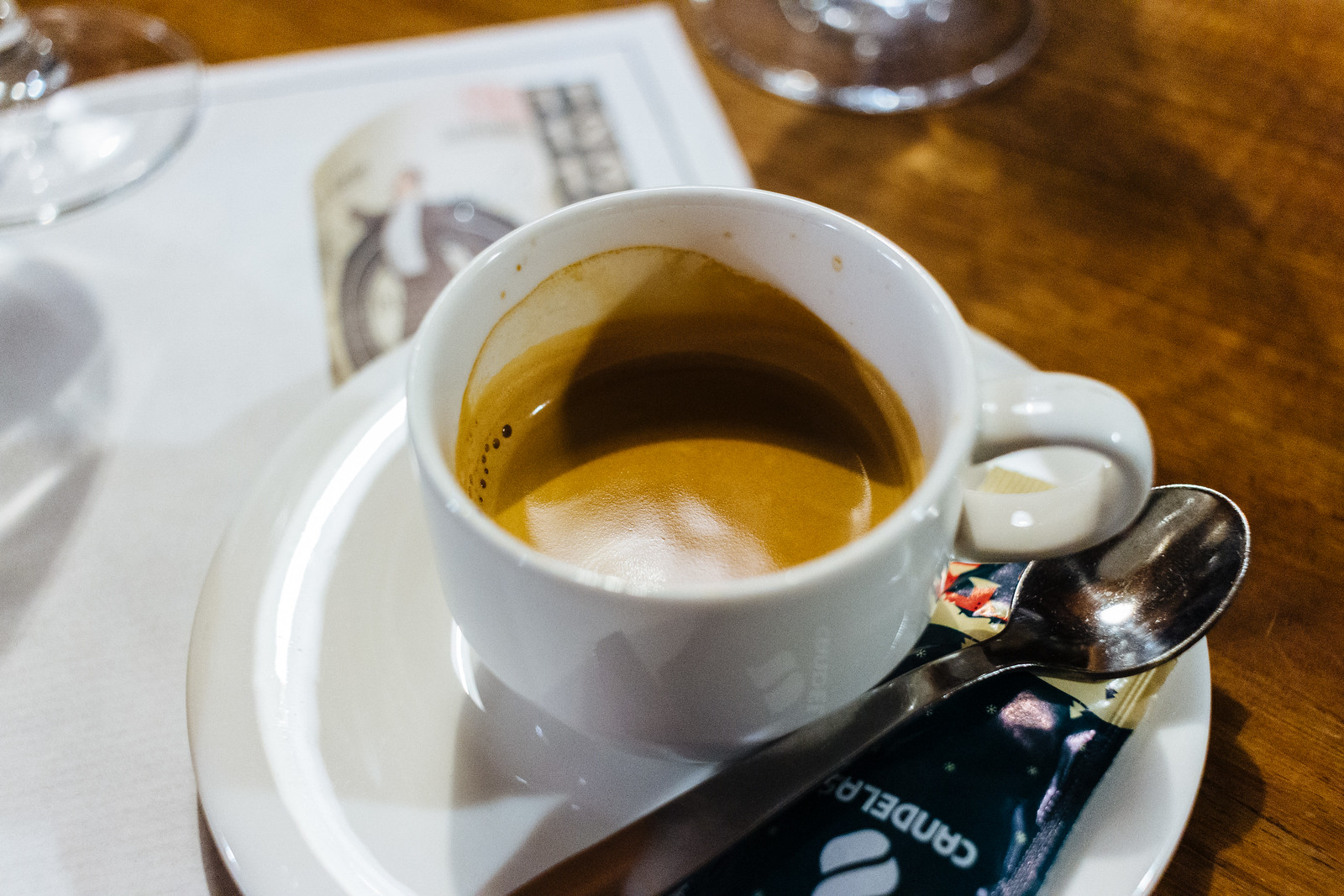 Shot of espresso in a white ceramic cup on saucer with spoon and sugar