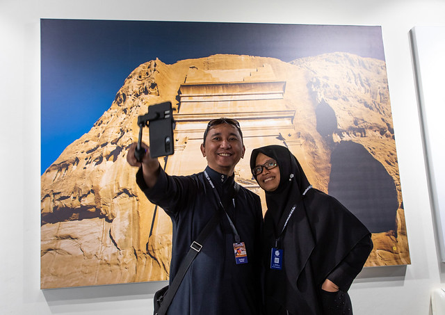Indonesian tourists taking a selfie in front of a picture of Madain Saleh, Al Madinah Province, Alula, Saudi Arabia
