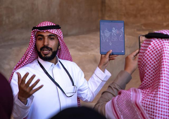 Saudi guide with tourists in Madain Saleh, Al Madinah Province, Alula, Saudi Arabia