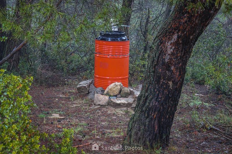 Barril metálido a los pies de un árbol en el camino de Mas de Bondia a Guimerà