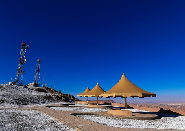Cellular transmission towers and umbrellas at the top of a hill, Al Madinah Province, Alula, Saudi Arabia