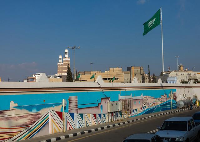 Saudi arabian flag in front of a fresco, Asir province, Abha, Saudi Arabia