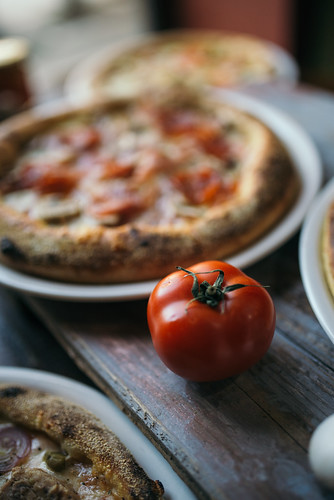 Close-up of a fresh tomato next to a pizza in a restaurant | by Ivan Radic