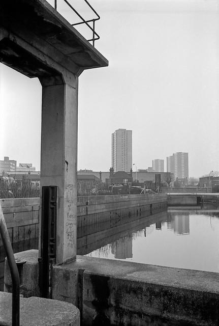 River Wandle, Wandsworth. 1982 30i-21: river, sluice, flats,