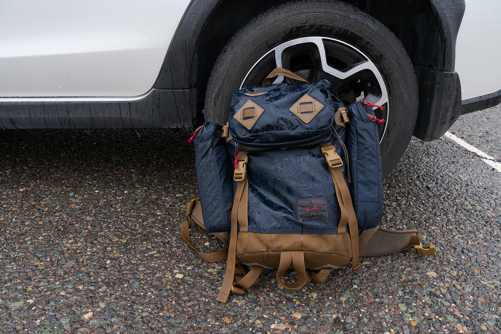 My rain-soaked Tom Bihn The Guide's Pack sits beside the back wheel of my 2013 Subaru Crosstrek at Cave Creek Regional Park in December 2019