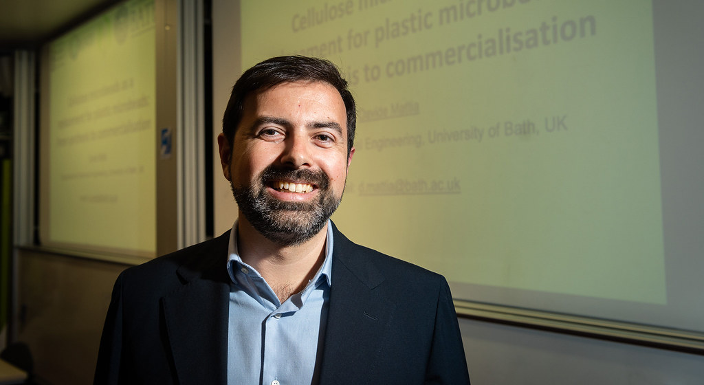 Professor Davide Mattia smiles in front of a powerpoint presentation on cellulose