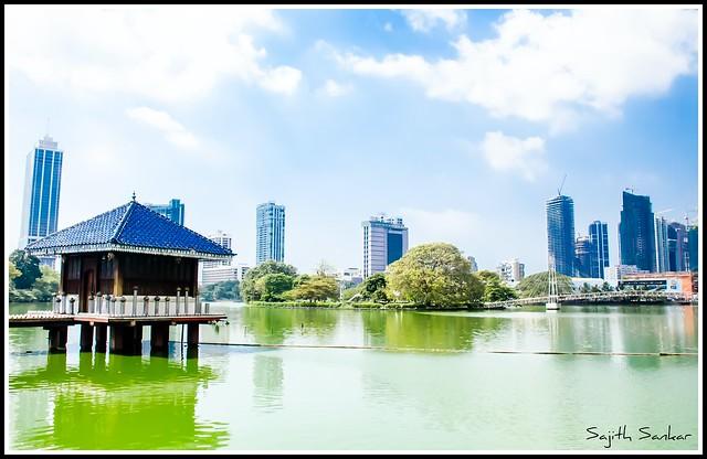 Colombo/Srilanka December 27th 2019: VIew of Gangaramaya lake temple in Colombo Srilanka. City skyscrapersc can be seen behind.