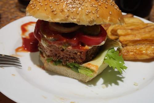 Vegetarischer Burger mit Beyond Meat Burger Patty, selbstgebackenem Sesam-Bun und mit Sekt geschmolzenem Cheddar (angeschnitten)