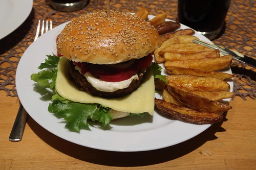 Frittierte Kartoffelspalten zu vegetarischem Burger mit Beyond Meat Burger Patty, selbstgebackenem Sesam-Bun und mit Sekt geschmolzenem Cheddar (zusammengebaut)