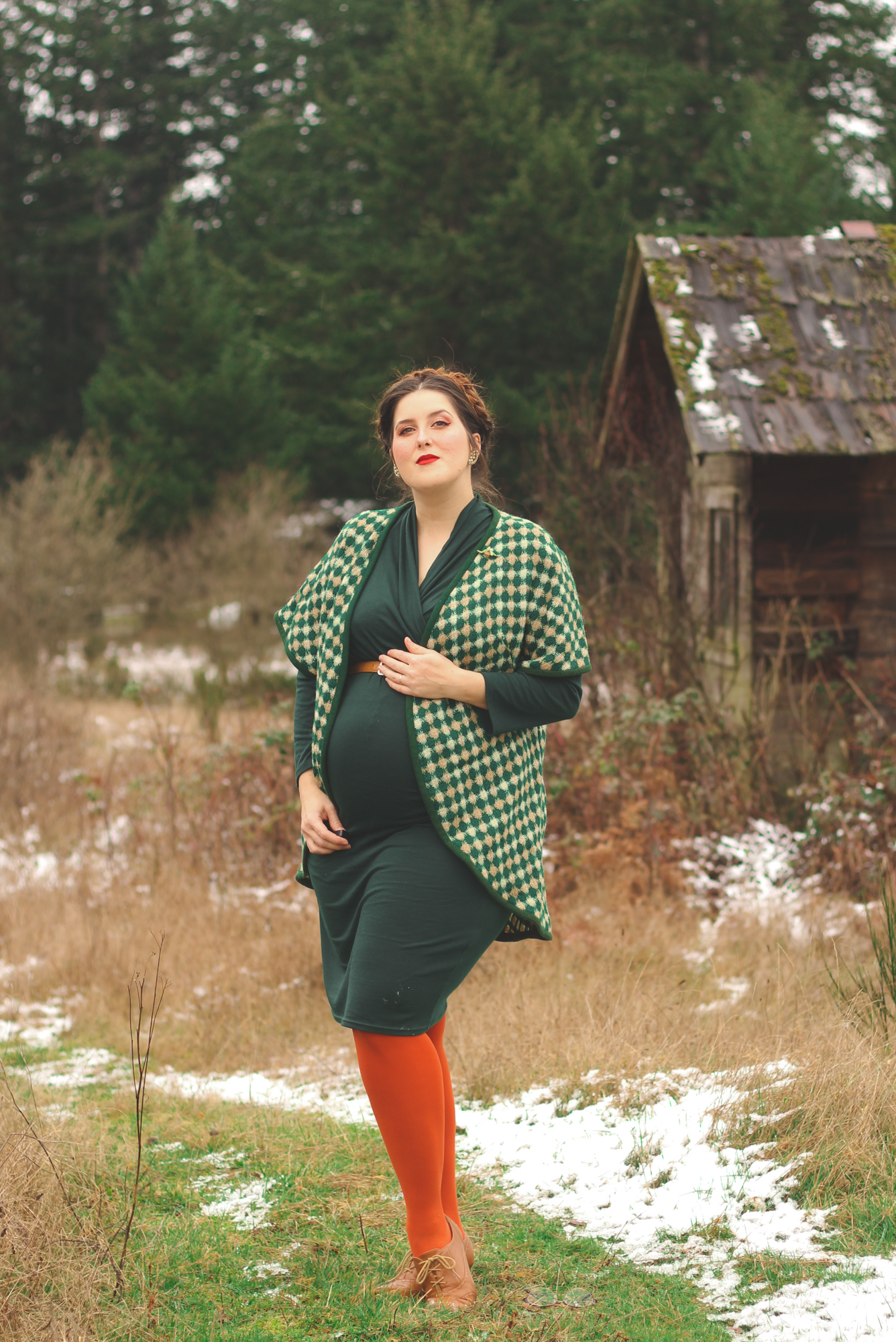 woman wearing green plaid and showing how to style maternity for winter