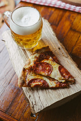 Beer and pizza on display in a restaurant on a rustic table on a wooden plank