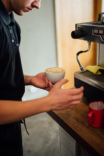 Barman holding a cup of espresso coffee in preparation