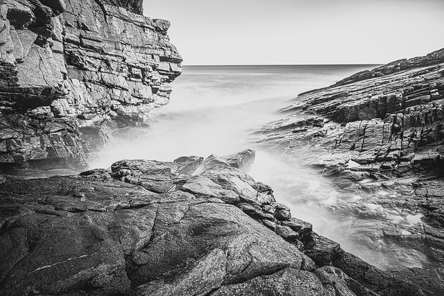 Rocks and cliffs at 3 angles to cup the North Sea - Collieston, Aberdeenshire, Scotland. Black & white fine art.