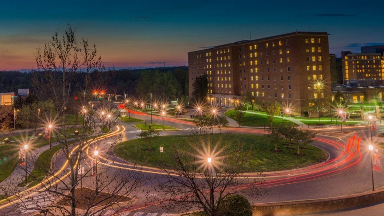 A university building at dusk, with light trails from moving vehicles