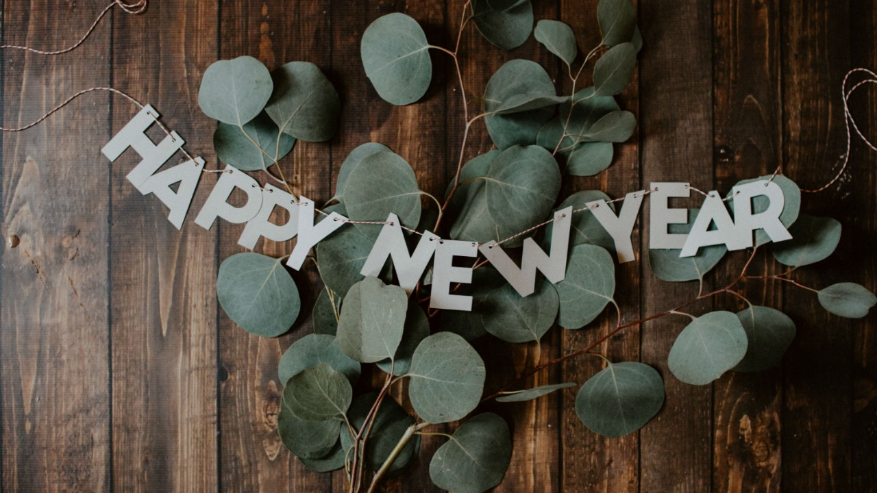 A decoration saying Happy New Year, laid out over some leaves