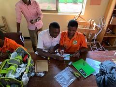 ASYV - Narcisse assisting a student in putting together the EKG Simulator Kit - Blake