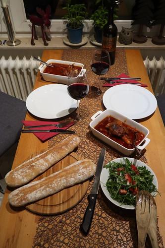 Lammhaxen in Tomatensoße mit frisch gebackenem Baguette und Ruccola-Salat (Tischbild)