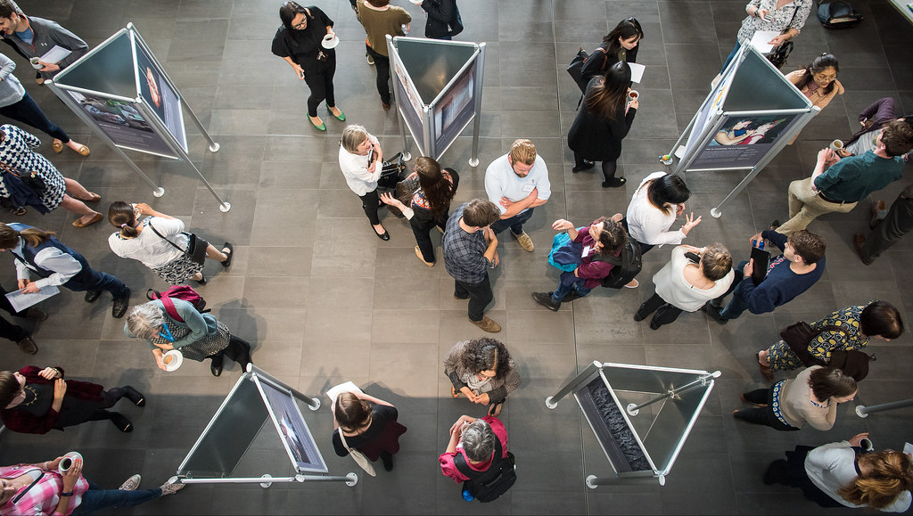 People discussing posters at an exhibition