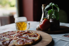 A closeup of a small pizza with a glass of beer next to it displayed on a table with nice decoration in the background