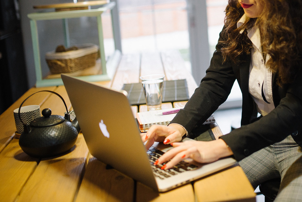 A suited businesswoman working on her laptop indoors with a teapot by side