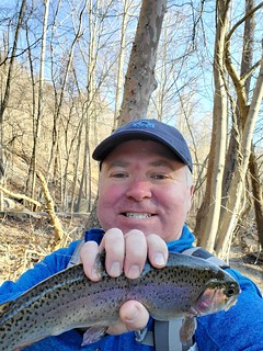 Photo of man holding a trout he caught in the Patapsco River