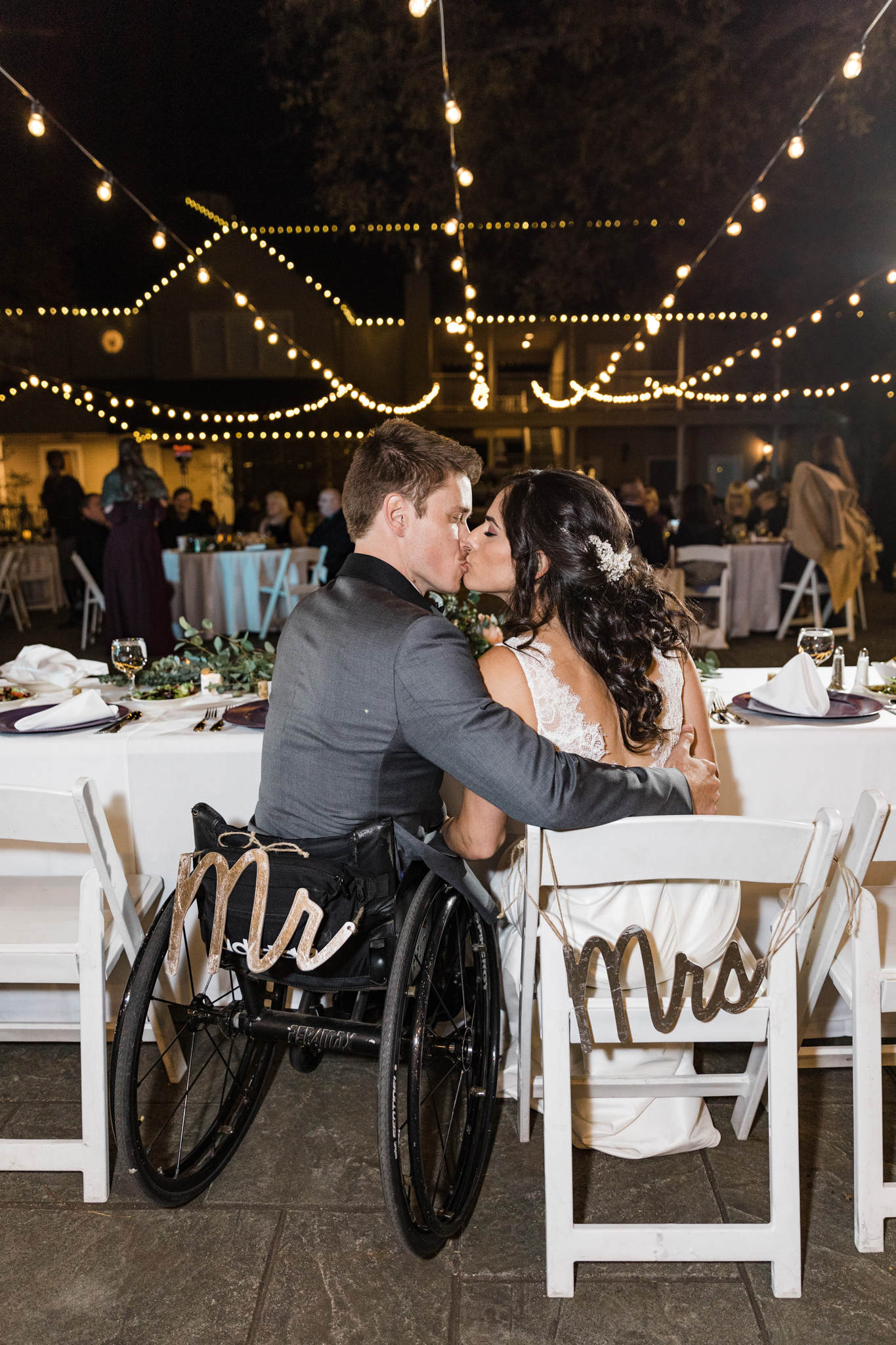 bride and groom in wheelchair share a kiss during their wedding reception
