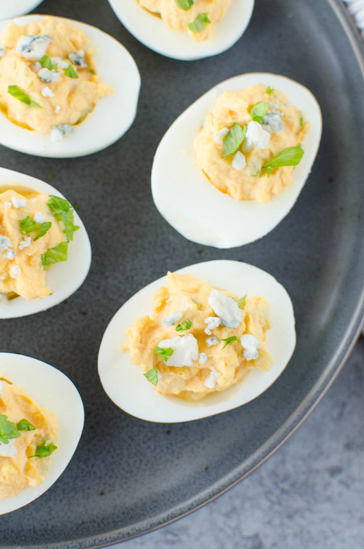 Buffalo Deviled Eggs - spicy buffalo deviled eggs topped with blue cheese. Perfect for a party!