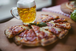 Beer and pizza on display in a restaurant on a rustic table with focus on the glass of beer | by shixart1985