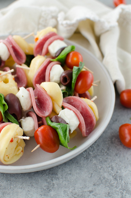 Antipasto Skewers - the easiest party appetizer! Cheese tortellini, Genoa salami, mozzarella balls, fresh basil, olives, and grape tomatoes layered on skewers.