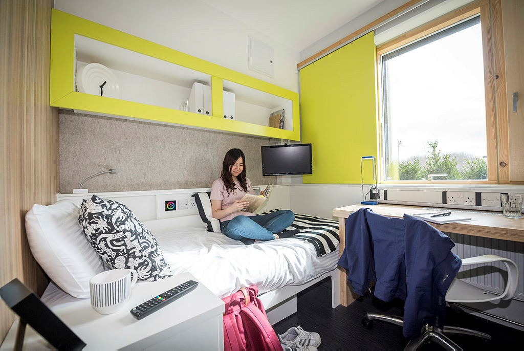 A student reading a book sat on a bed in student accommodation