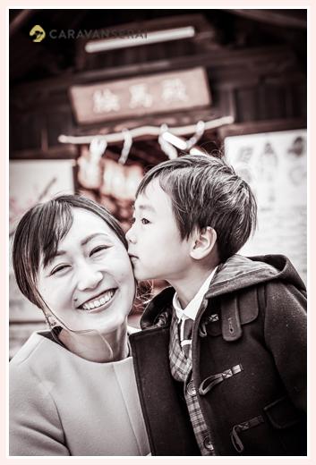 ママの頬にキスする男の子 冬の神社にて