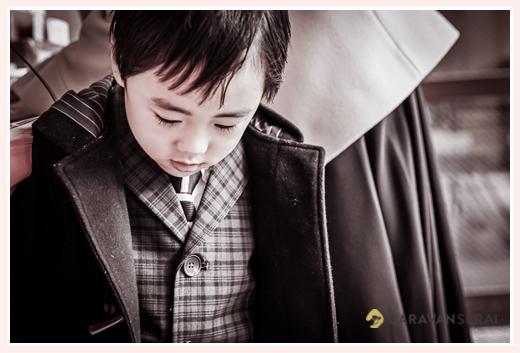 スーツとコートを着た(正装した)男の子 モノクロ写真