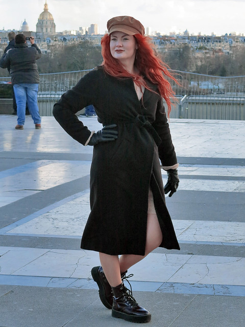 Red-haired lady posing with black coat, beret and gloves