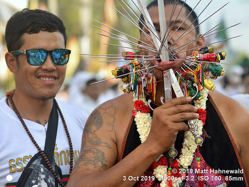 matthahnewaldphotography facingtheworld qualityphoto character head face cheek mouth lower lip extreme piercing expression emotional graphiccontent conceptual dedication religion impact spiritual traditional cultural festival celebration devotee worshiper person friends male young man background primelens nikond610 nikkorafs85mmf18g 85mm 4x3ratio resized 1200x900pixels horizontal street doubleportrait closeup halflength fullfaceview colour authentic mahsong masong vegetarianfestival nineemperorgods pain parade jiachai ritual taoist pin needle skewer sword tradition phukettown thailand thaichinese asian holding flower garland apron right hand lookingcamera tattoo clarity