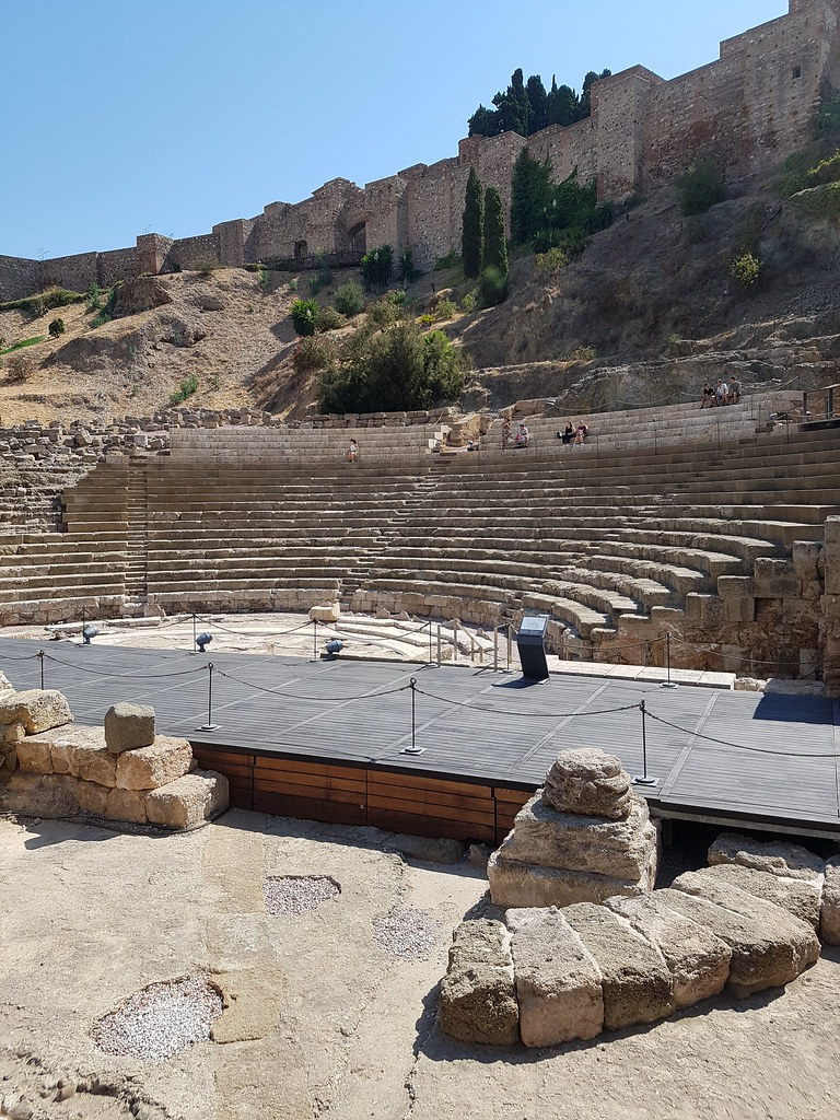 A view of the old ruins of the Roman theater. You can see the amphitheater stone seating area going up, with the panorama of the Alcazaba walls behind it. There is a walkway in the middle.