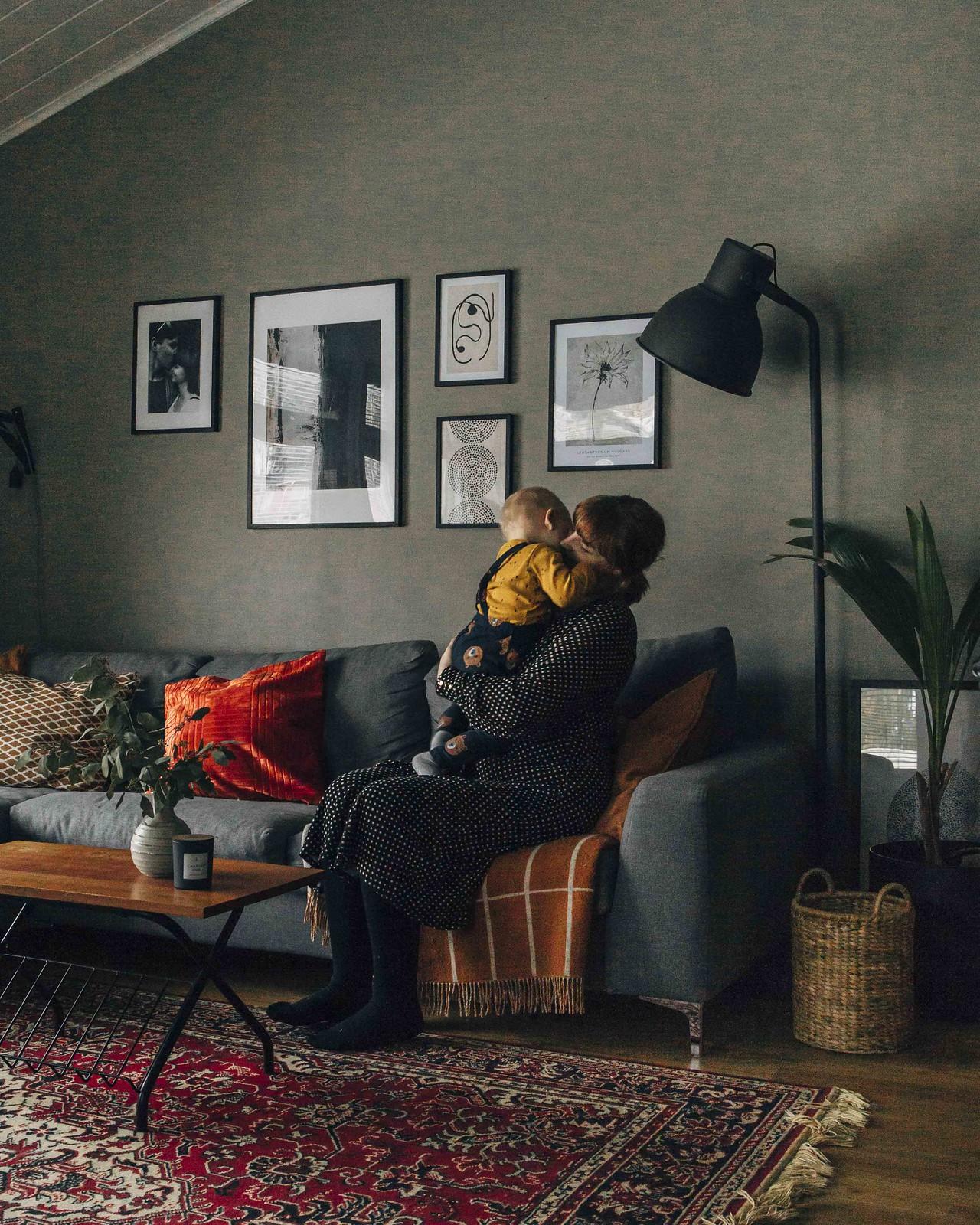 Nainen istuu harmaalla sohvalla ja halaa taaperoa.