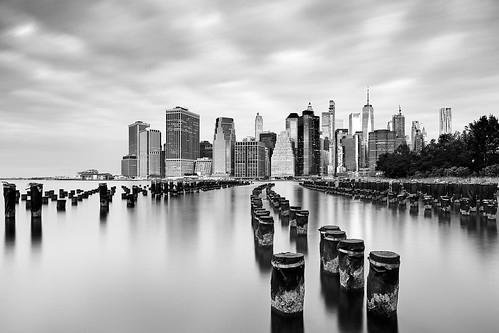 urban urbanphotography city cityscape waterscape water river poles reflection waterfront skyline highrise skyscraper trees cloudy sky clouds overcast curve earlymorning aftersunrise goldenhour longexposure neutraldensityfilter nd gnd breakthroughphotography x4nd10 tiffen gradnd sirui canon 7dmarkii efs1018mm unitedstatesofamerica unitedstates usa us newyork newyorkcity ny nyc brooklyn manhattan lowermanhattan brooklynbridgepark oneworldtradecenter blackandwhite monochrome
