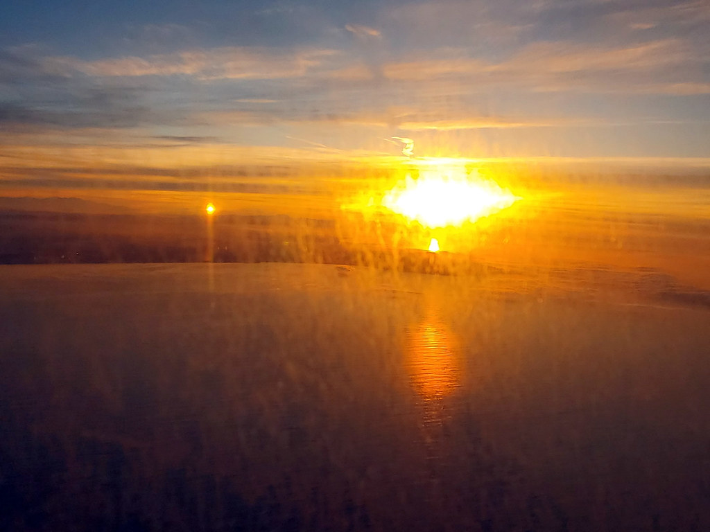 Sunrise on the Pacific Ocean through a dirty airplane window