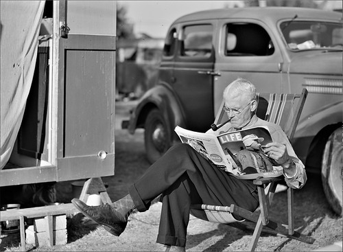 Easy Life: Winter tourist reading a magazine beside his trailer home. Sarasota trailer park, Sarasota, Florida, January 1941.