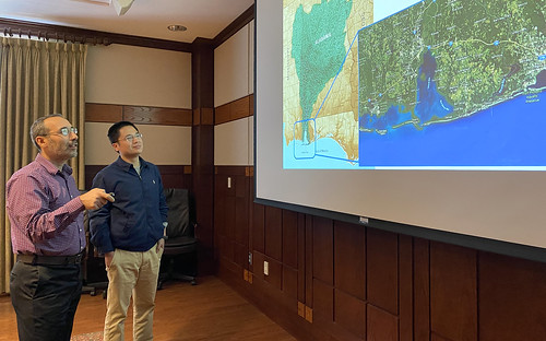 Latif Kalin and Di Tian look at a map of Mobile Bay