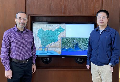 Latif Kalin and Di Tian stand next to a map of Mobile Bay.