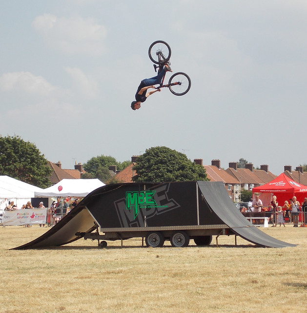 STUNT CYCLIST PERFORMING DARING MOVES ON A BICYCLE OVER A RAMP AT A MUSIC FESTIVAL IN AN EAST LONDON BOROUGH SUBURB STREET PARK VENUE ENGLAND DSCN1882