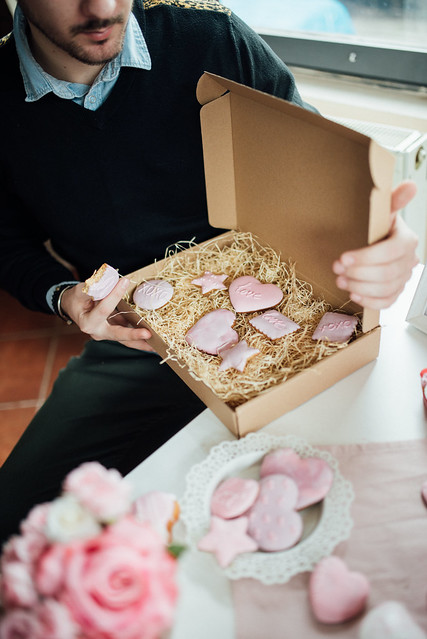 The young man opens a box of Valentine cakes.