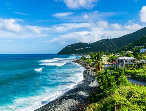 britishvirginislands caribbean sea mountains sky telephonewires rockybeach palmtrees waves clouds hills ocean